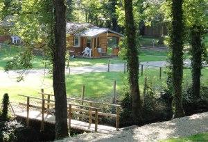 Chalet d'un camping moderne dans un cadre verdoyant avec ruisseau